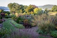 View over flower beds with ornamental grasses and mown path to countryside beyond