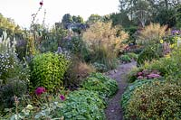 View along narrow path with wide beds full of perennials