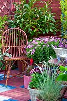 Wicker chair on patio with potted spring containers