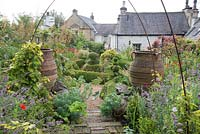 Overview of cottage garden with topiary, large urns and informal borders.