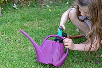 Girl filling a purple plastic watering can from a hose