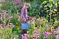 Woman with a watering can in kitchen garden.