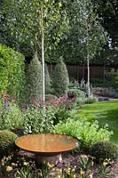 Rust effect water bowl in garden with white stemmed birch trees, Pittosporum tenuifolium 'Silver Queen', Astrantias, Sedums and Agastache - July, Cheshire