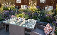 Outdoor acrylic rattan dining furniture with table and chairs with orange cushions on patio surrounded by a lucent copper slate raised bed with colourful planting of yellow and purple flowering plants, ornamental grasses with rusted corten steel screens. The RNIB Community Garden. RHS Hampton Court Flower Show July 2018  - Designer: Steve Dimmock and Paula Holland - Sponsor RNIB, Magus Private Wealth