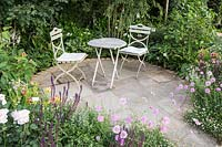Cottage garden with a round patio with small table and chairs, surrounded by beds with: Scabiosa incisa 'Kudo', Salvia nemorosa, roses, hostas and Erigeron karvinskianus. BALI Best of Both Worlds Garden