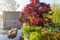 Office studio in front of reflective black pond water feature on a misty May spring day - mixed planted border with grasses ferns and green foliage plants - Acer palmatum 'Bloodgood' Garden of Quiet Contemplation garden. RHS Malvern Spring Festival 2019  - Designer Peter Dowle - Leaf Creative