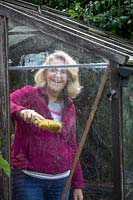 Cleaning greenhouse glass with a brush before winter