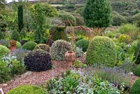 Topiary shapes in formal area of cottage garden in September