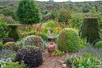 Small formal area of cottage garden with views of landscape beyond