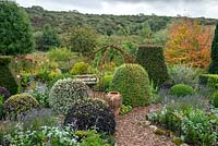 Topiary in country garden with views to landscape beyond in September