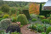Formal area of cottage garden with views to landscape beyond in September