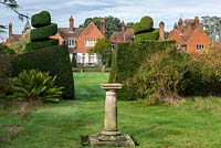 View between yew hedging and topiary to large country house beyond