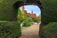View through large yew arch to country house