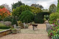 The terrace with views through a monumental yew arch to twin borders