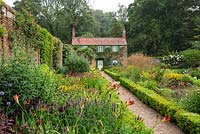 An old cottage overlooks the walled Spider Garden at Hoveton Hall. A gravel path separates herbaceous borders edged in box hedges.