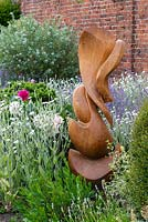 Wooden sculpture by Peter Leadbeater in a herbaceous border of Lychnis coronaria 'Alba', catmint and Peonies.