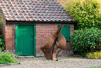A contemporary sculpture in front of an old potting shed