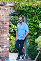 Nic Howard, garden designer, in the doorway leading into his courtyard.