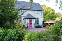 A contemporary country cottage with front garden, brick drive, wood store with green roof and mixed border planted with hydrangeas, box and perennials.