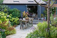 A contemporary courtyard garden with dining area, summerhouse and mixed border with shrubs, perennials, grasses and ferns.