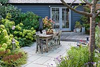 A contemporary courtyard garden with dining area and summerhouse