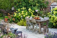 A contemporary courtyard garden with dining area surrounded by mixed border with shrubs, perennials, grasses and ferns