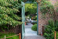 Open gate leading to  contemporary walled cottage garden