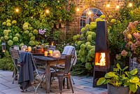 A dining area in a courtyard garden lit by a string of bulbs and candles, heated by a modern outdoor chimenea. Planting behin includes Hydrangea 'Limelight', Rosa 'Blush Noisette', Anemone hybrida 'Elfin Swan' and ferns.