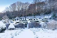 View from the Grasses Parterre to the snow covered Hedge Gardens and wood in background. Hedges and columns of taxus baccata and wave-form hedge of Fagus sylvatica in foreground. Veddw House Garden, Monmouthshire