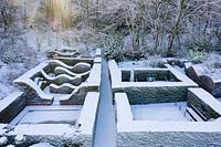 Formal country garden overview - snow covered topiary hedges. Garden - Veddw