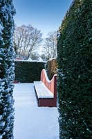 Snow-covered seat in the Reflecting Pool. Garden – Veddw