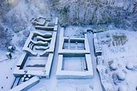 Drone overview of formal country garden covered in snow. Garden - Veddw
