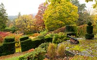 A boat race starting canon on a stone terrace overlooking taxus baccata and  autumn foliage at High Moss, Portinscale, Cumbria, UK