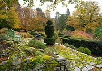 A moss covered stone terrace with a view over cloud shaped Taxus baccata and Buxus and autumn foliage on Quercus at the Arts and Crafts garden, High Moss, Portinscale, Cumbria, UK
