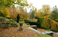 A view from a terrace over cloud shaped Taxus baccata, Buxus, and Fagus sylvatica High to autumn foliage at the Arts and Crafts garden at High Moss, Portinscale, Cumbria, UK