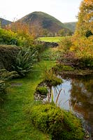 A pond surrounded by mounds of moss, and autumn foliage with a view toward The Tongue in the northern fells