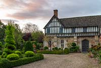 At dawn, a part timbered Mediaeval manor house flanked by a formal box parterre, seen past an island bed of clipped topiary.
