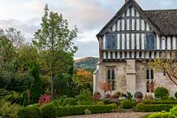 A glimpse of Cooper's hill beside the facade of a part timbered, Mediaeval manor house overlooking a formal box parterre.