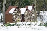 Rusted metal storage houses with wood in the snow.