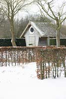 Gardenhouse with round window behind hedges in the snow.