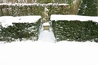 Classic garden figurative statue in between hedges covered with snow.