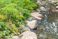 Shallow stream in woodland garden with edging of rocks and pebbles. The Zoflora and Caudwell Children's Wild Garden. RHS Hampton Court Palace Flower Show, 2017. Designers: Adam White and Andree Davies.