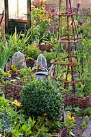 Small vegetable plot with decorative willow edging, obelisk and wire cloches to protect from animals such as birds and rabbits.