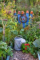 Vegetable and flower beds in late summer with a watering can.