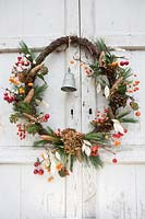 Pine wreath of berries, cones, seed heads and metal bell, hanging on a rustic wooden door