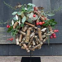 Wooden globe decorated with crab apples and evergreen foliage. Styling: Marieke Nolsen