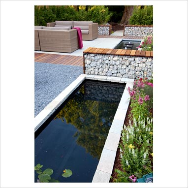 0209127   Small Raised, Rectangular Pond And Bench Made From Gabions In  Modern Garden. Patio With Sofas Beyond.