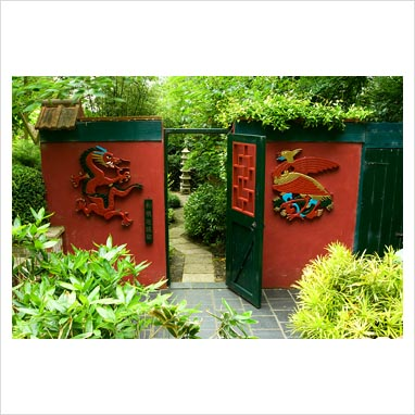 Three-Friends-of-Winter garden has a winter flowering plum, Prunus mume, at its centre and Sasa veitchii - Bamboo. Hand carved Phoenix and dragon flank gate into Red Wall Garden. Beggars Knoll, Newtown, Westbury, Wiltshire, UK